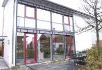 赤とグレーの色使いがおしゃれな外観、赤いフレームの窓や扉は開閉できる